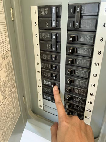 This picture shows an electrical panel installation in Livermore. The electrician is testing the circuit breaker after install.